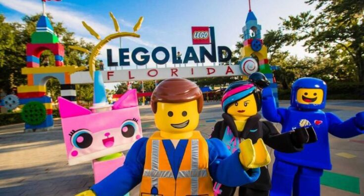 Unikitty-Emmet-Wyldstyle-and-Benny-from-THE-LEGO-MOVIE-WORLD-posing-in-front-of-Legoland-Florida-entrance-e1566208058128